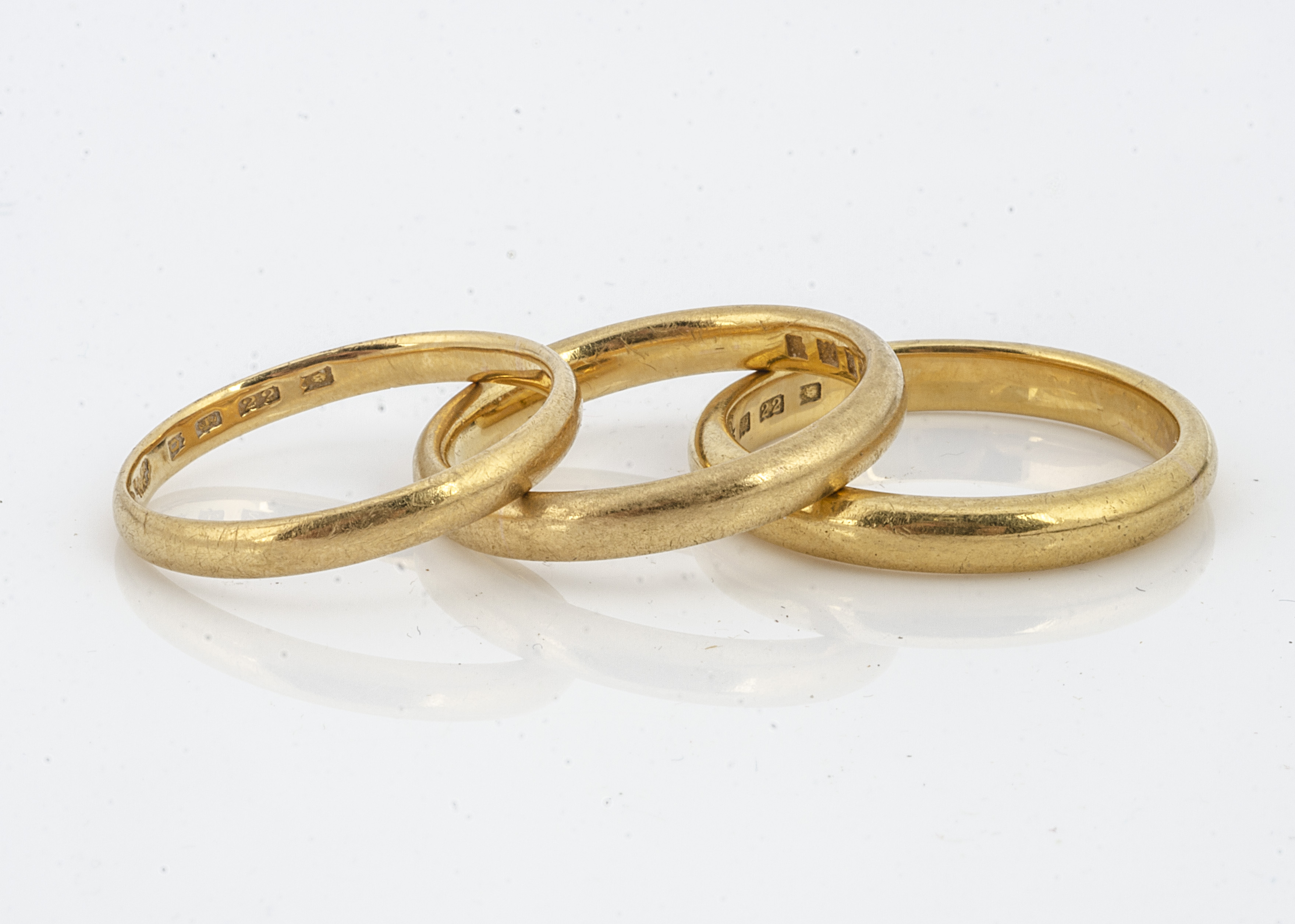 Three 22ct gold D shaped wedding bands, one size S, 2 x size P, 13.7g