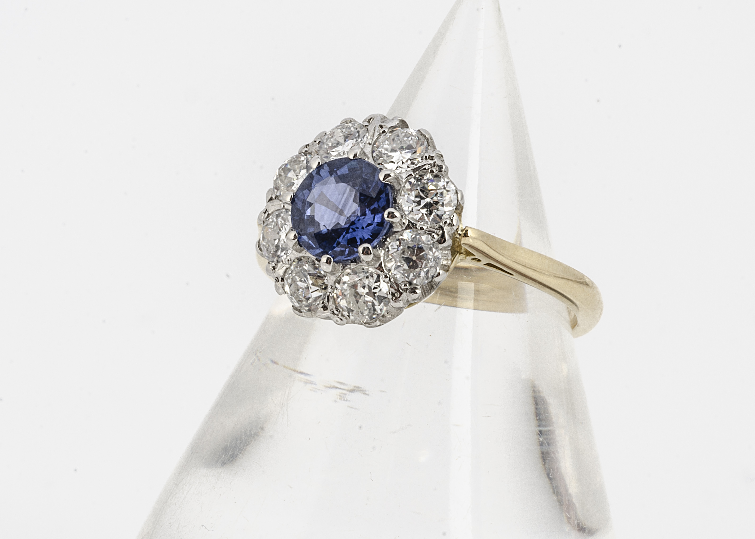A yellow gold and sapphire and diamond set cluster ring, the circular mixed cut central sapphire