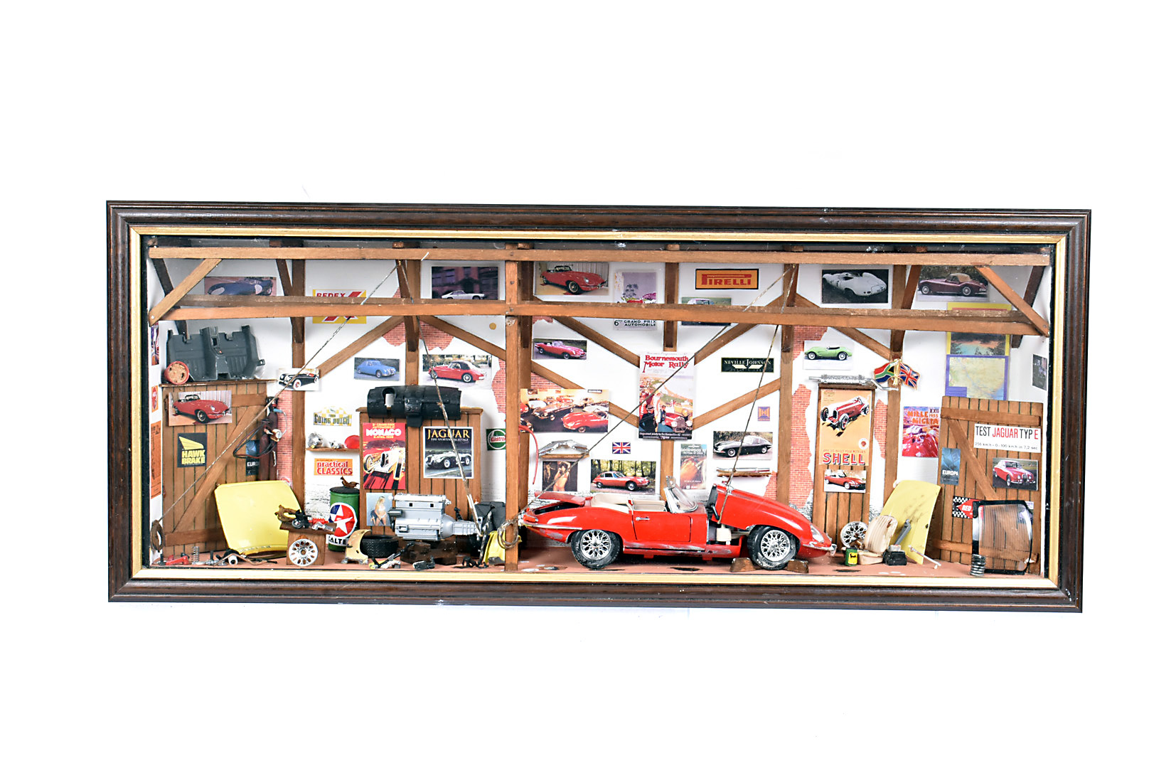 A Jaguar Garage Diorama, the workshop featuring a red Jaguar E-Type being worked on, with the engine