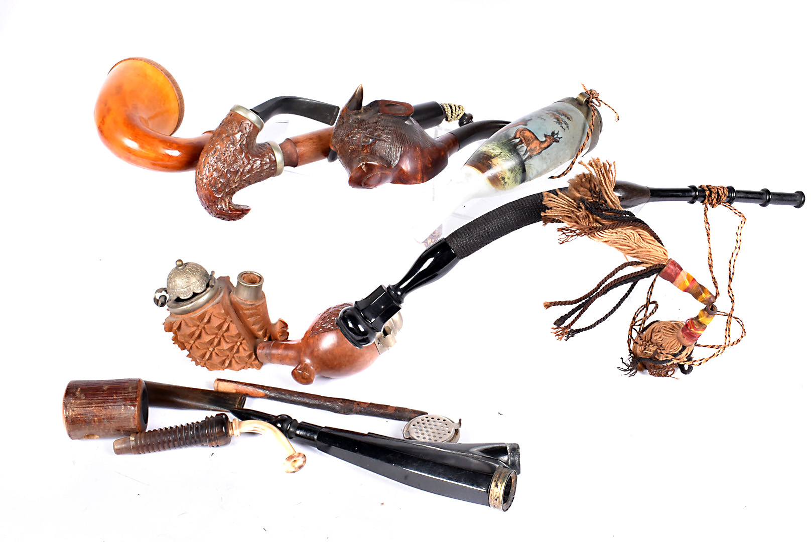An assortment of Continental smoking pipes, including a porcelain example, decorated with a stag and