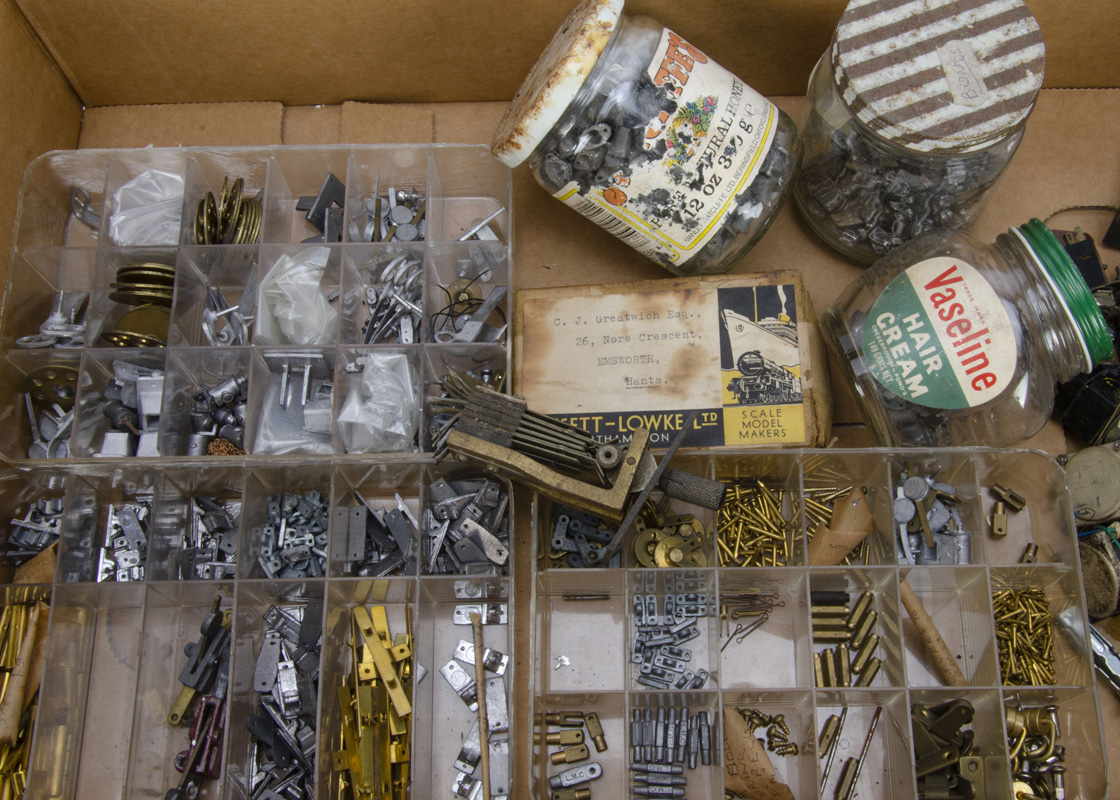 An assortment of vintage 0 Gauge track and layout components, including white-metal track chairs,