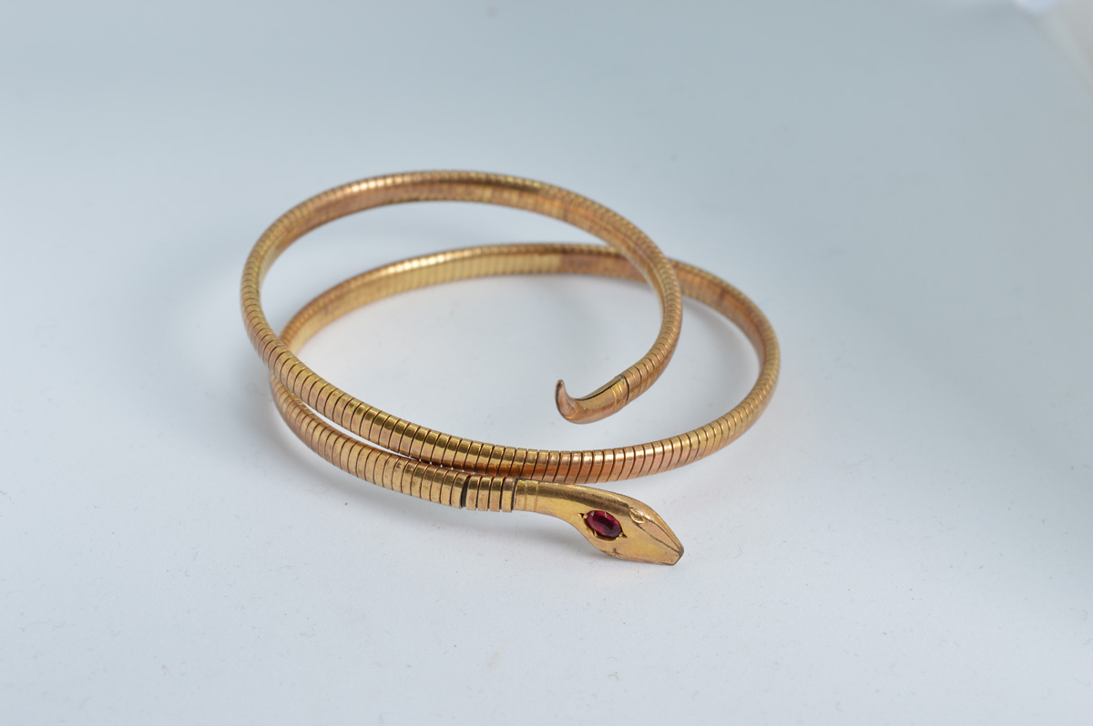 A rolled gold expandable Serpentine bangle, circa 1900, with red paste set head, marked Rolled