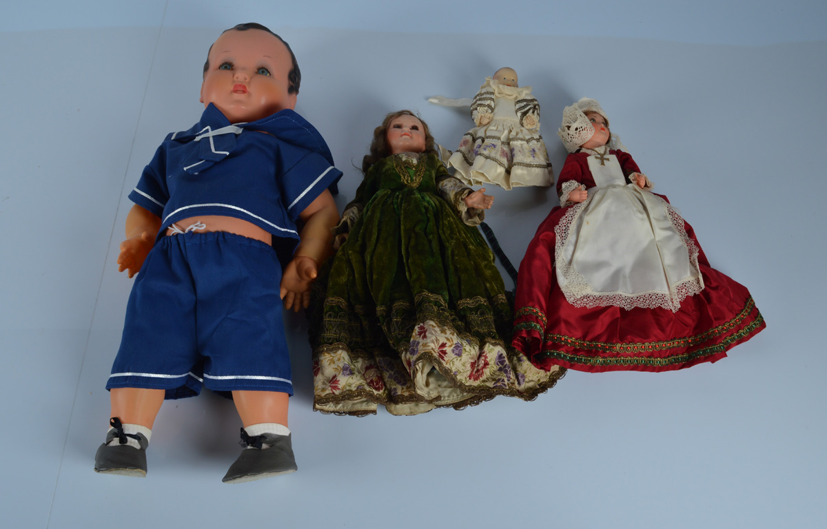 Four French celluloid dolls, a large boy marked on back with a windmill in a sailor's suit, 22