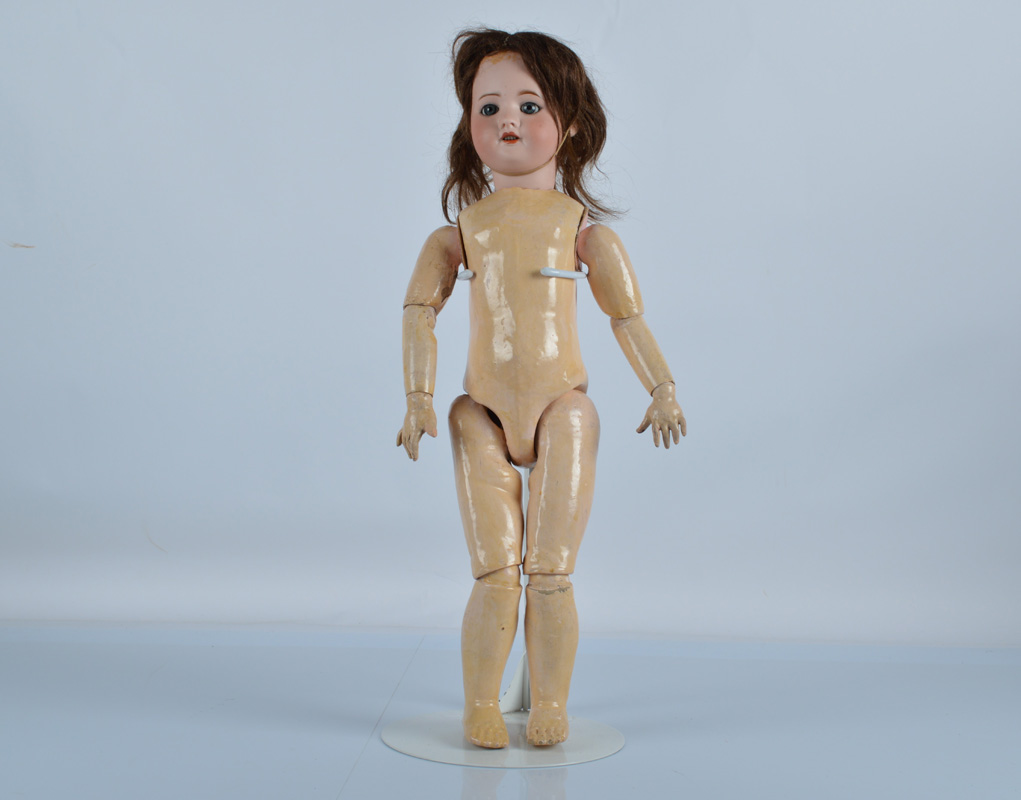An S.F.B.J 60 child doll, with blue sleeping eyes, brown hair wig, jointed papier mache body and