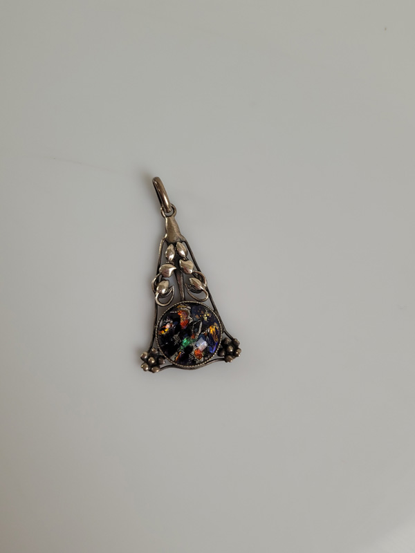 An Arts and Crafts silver and glass drop pendant, of triangular shape with pierced leaf floral