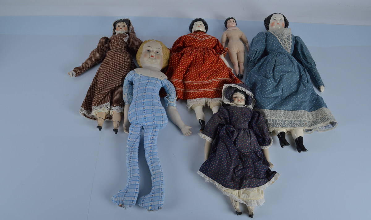 Five reproduction china shoulder head dolls, stuffed bodies, four dressed, 23 inch (58.5cm) high and