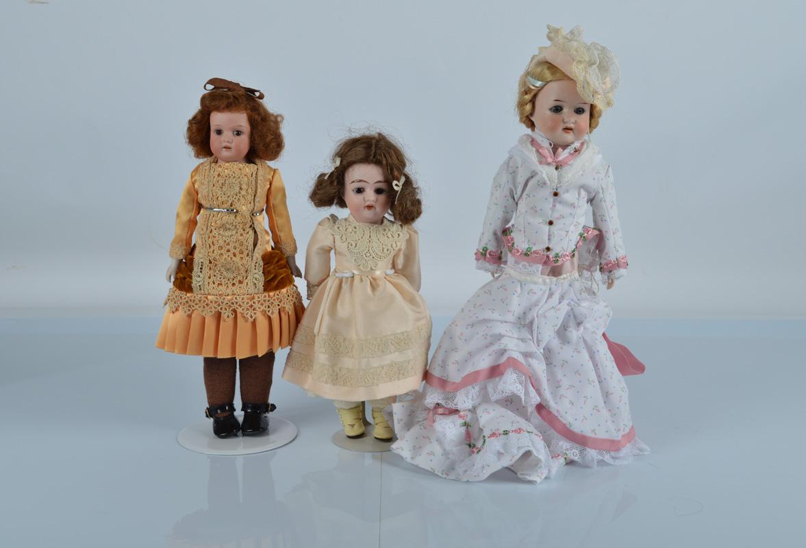 Three small German bisque shoulder head dolls, an AM 370 in orange dress, 12 1/2 inch (32cm) high,