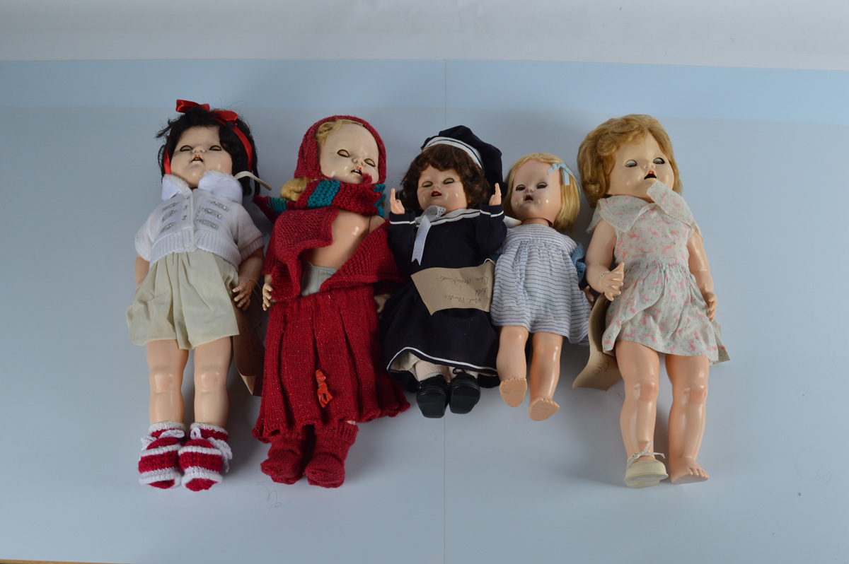 Five hard plastic child dolls, all with weighted eyes, one with squeak, one in crimson red skirt and