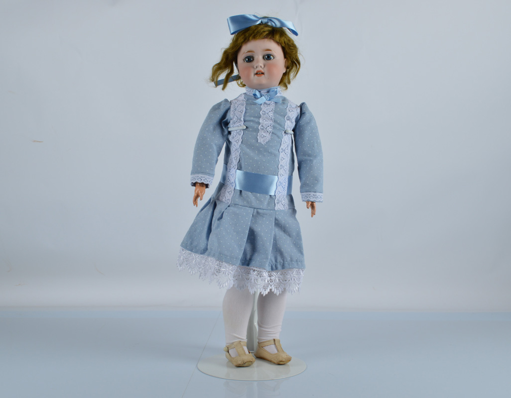 A Schoenau and Hoffmeister 1909 child doll, with blue sleeping eyes, brown mohair wig, jointed