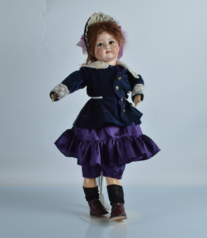 A Schoenau and Hoffmeister 1909 child doll, with brown sleeping eyes, brown mohair wig, jointed
