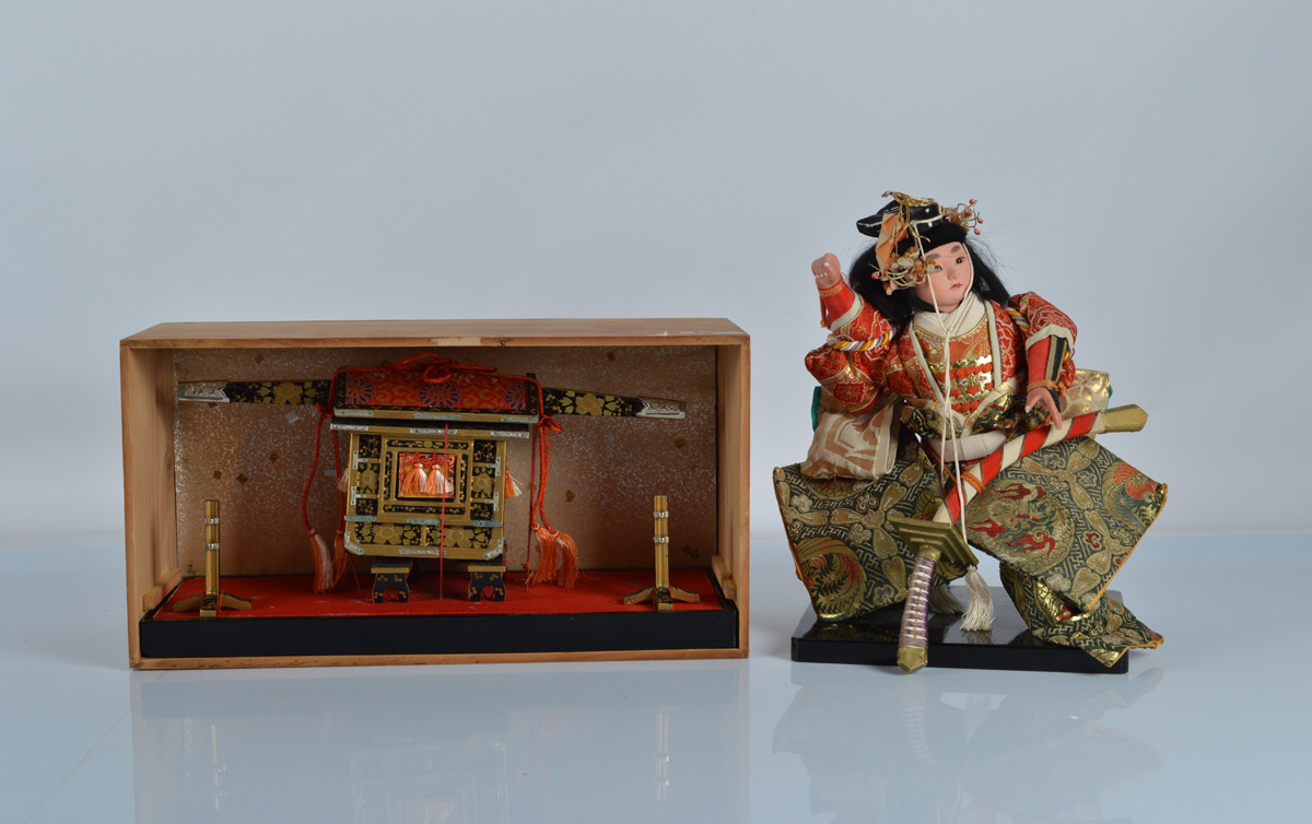 A Japanese pink gofun boy samurai in elaborate clothing on stand, 12 inch (30.5cm) high and a