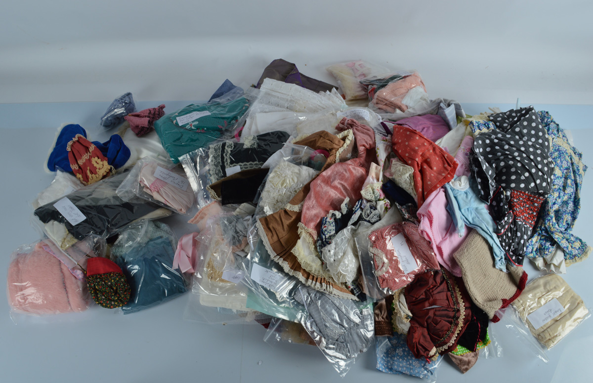 A quantity of dolls clothing, including a gingham dress, silk example