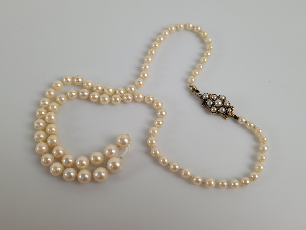 A string of graduated cultured pearls on a 9ct gold clasp, the knotted strung pearls af to centre,