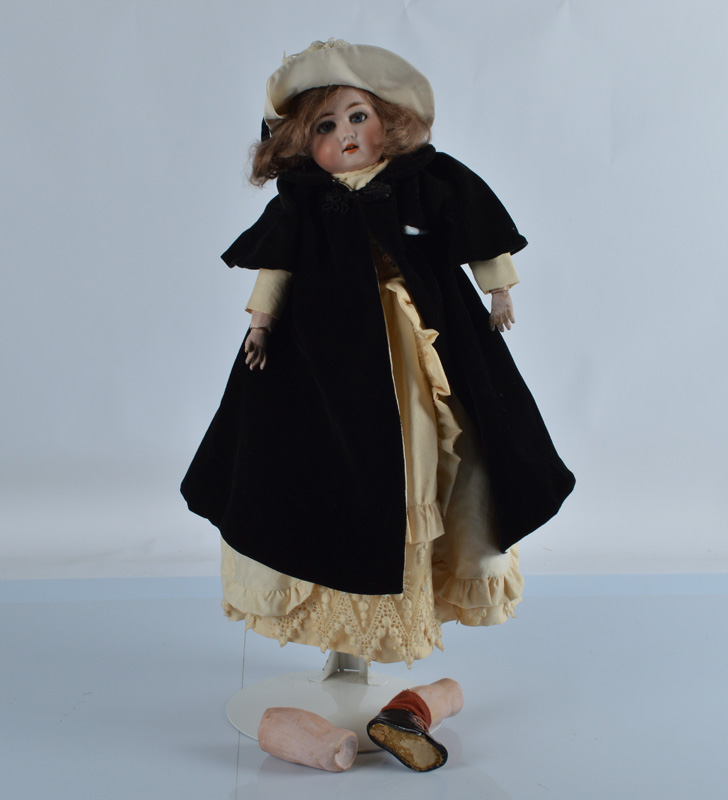 A Simon & Halbig child doll, with weighted blue lashed eyes, open mouth in a cream dress with