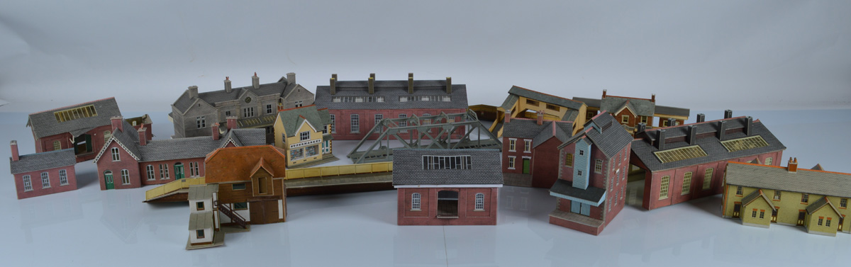 A large quantity of card kit built railway layout buildings, including houses, platforms, station