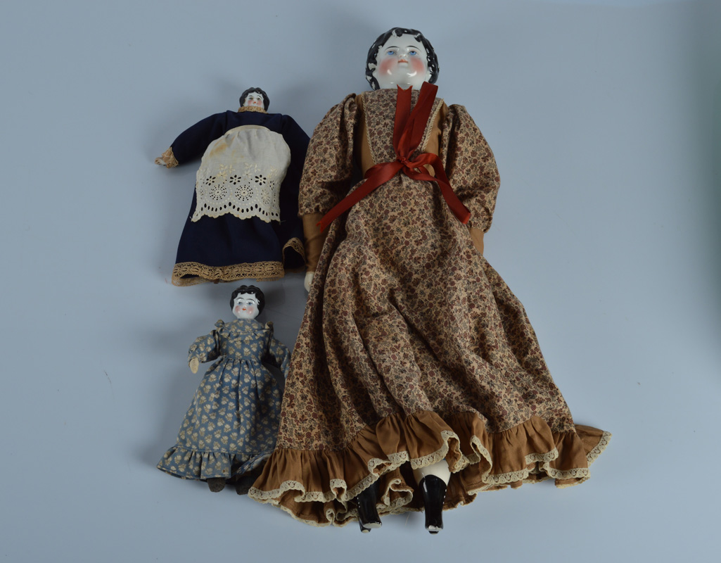 A china shoulder head doll, with blue painted eyes and black painted curly hair, on recent stuffed