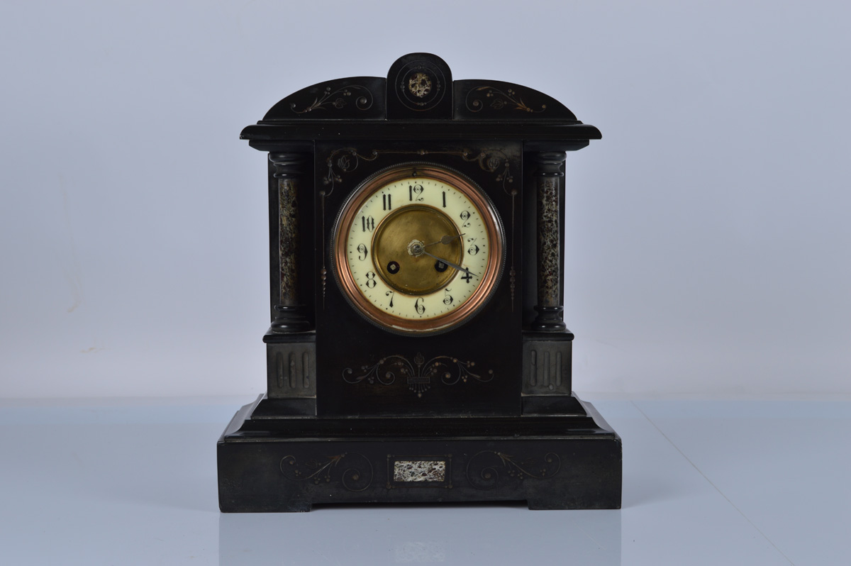 A slate mantle clock, with enamel and brass dial, marble pillars and inlay. Brass chiming movement