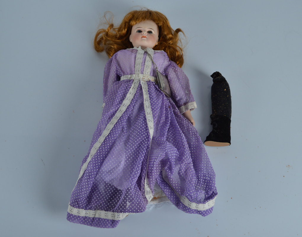 A German domed headed closed mouthed bisque shoulder head doll, with fixed striated blue glass eyes,
