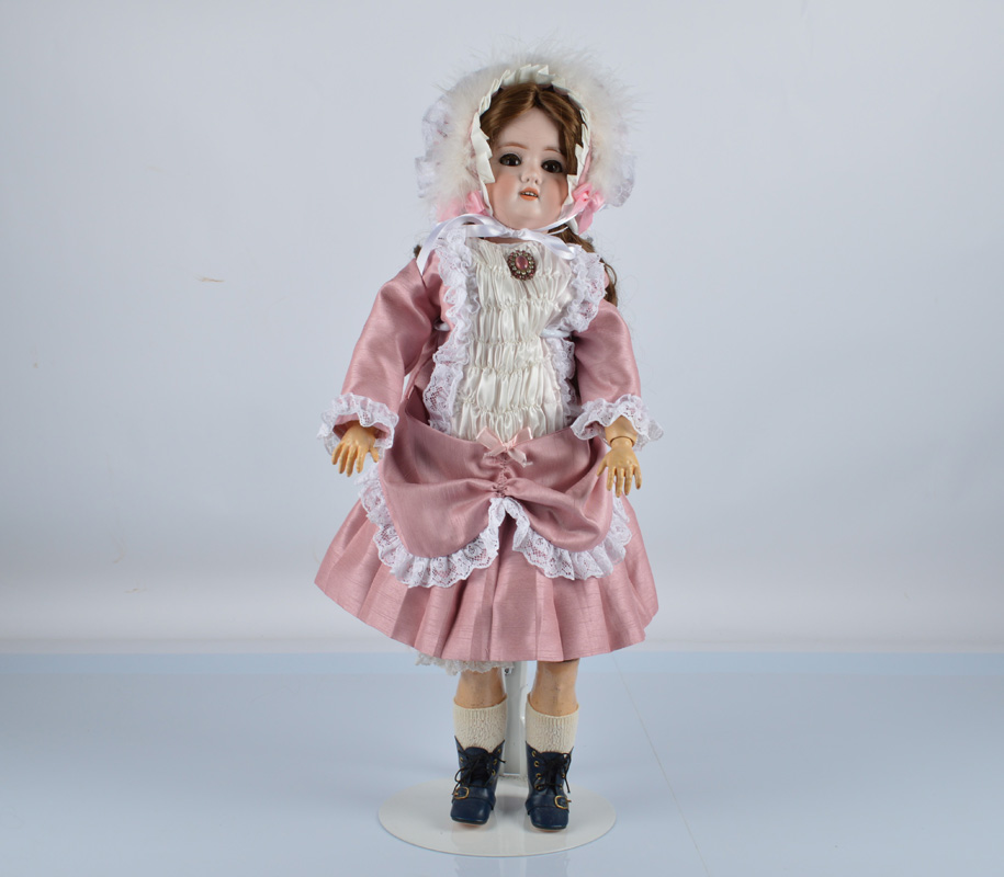 A Schoenau and Hoffmeister 1909 child doll, with brown lashed sleeping eyes, replaced brown wig,