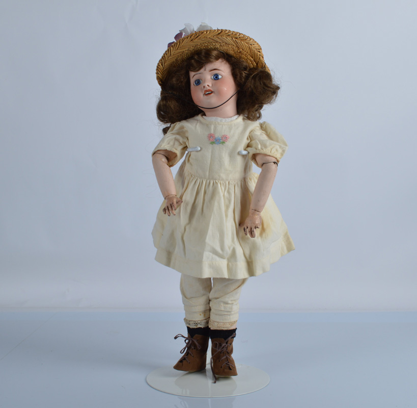 A SFBJ 60 child doll, with fixed blue eyes, replaced brown wig, jointed papier mache body, yellow