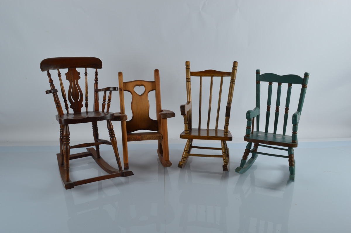 Four wooden doll rocking chairs, including one with heart shaped back splat