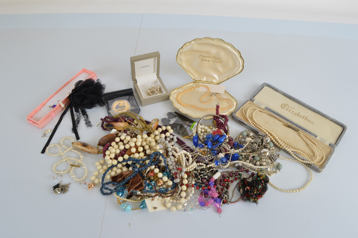 A collection of beads, including a cased set of simulated pearls, another in a shell case, small