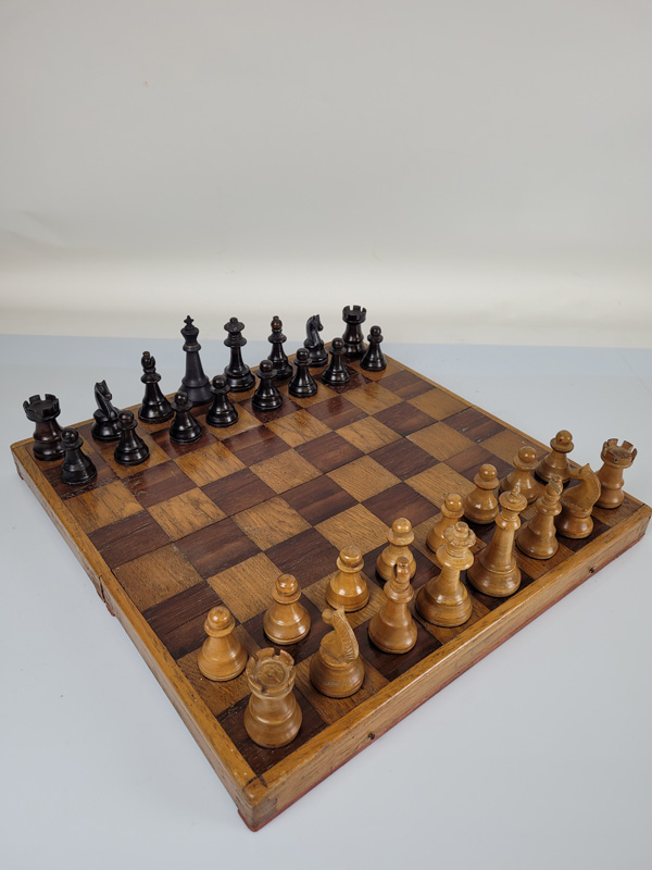 A weighted wooden chess set, with ebonised pieces and wooden board.
