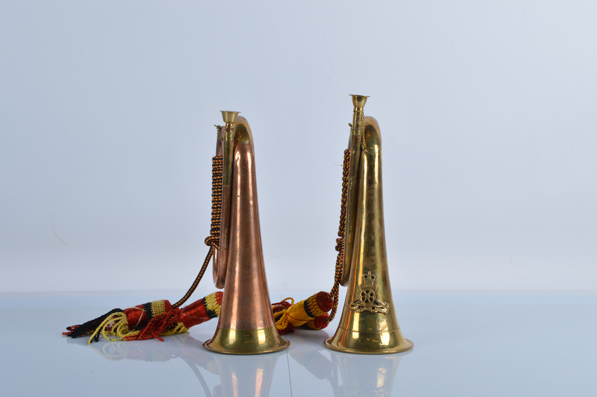 Two military bugles, one in copper with brass fittings, the other in brass with Royal Artillery