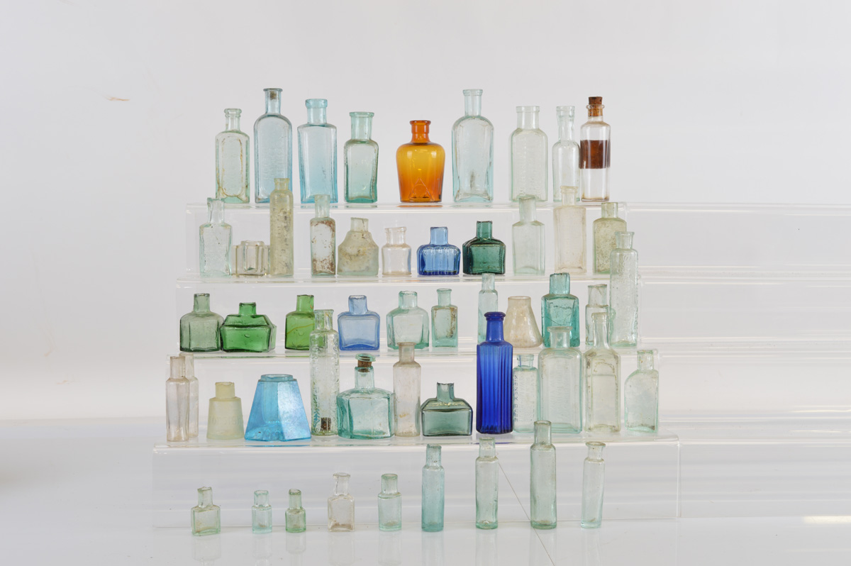 A collection of thirteen 19th century coloured glass ink bottles, of various shapes from conical,