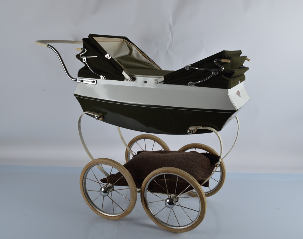 A vintage double canopy doll pram, in green and white in sprung base, on four rubberised spoke