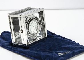 A modern silver plated desk clock from Aquascutum, square with glass panels and containing a ship'