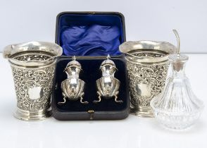A pair of late Victorian silver peppers in case, together with a pair of silver filled pierced vases