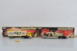 Two Scalextric Juggernaut slot car models, C301 Roadtrain and C302 Lowloader, both with boxes
