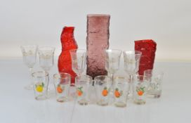 A collection of glassware, including three Whitefriars style vases, two red examples one of textured