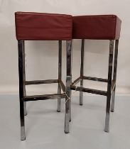 A pair of vintage stainless steel bar stools, rectangular form with red leather cushioned seats,