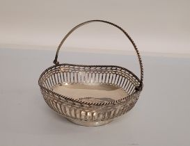 A George V silver swing handled pierced circular basket, of circular shape with shaped outline,