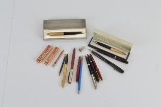 A collection of assorted fountain pens and pencils, including a Swan Mabie Todd and Parker Duofold
