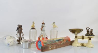 A mixed lot, including a set of scales, tins, spirit level, Schweppes soda syphon, miner's lamp,