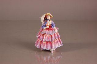 A c1935 Royal Doulton porcelain figure of a lady, HN 1579, The Hinged Parasol generally good