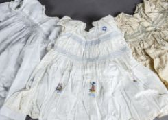 A collection of baby clothes, early 20th century, including smocked 1920s dresses and cotton