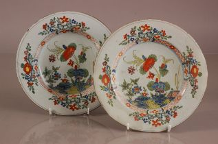 A pair of lat 18th or early 19th century French faience plates, 24cm diamter, some chips