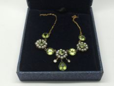 A boxed necklace set with peridots, seed pearls an