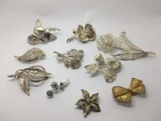 A collection of ten silver brooches.