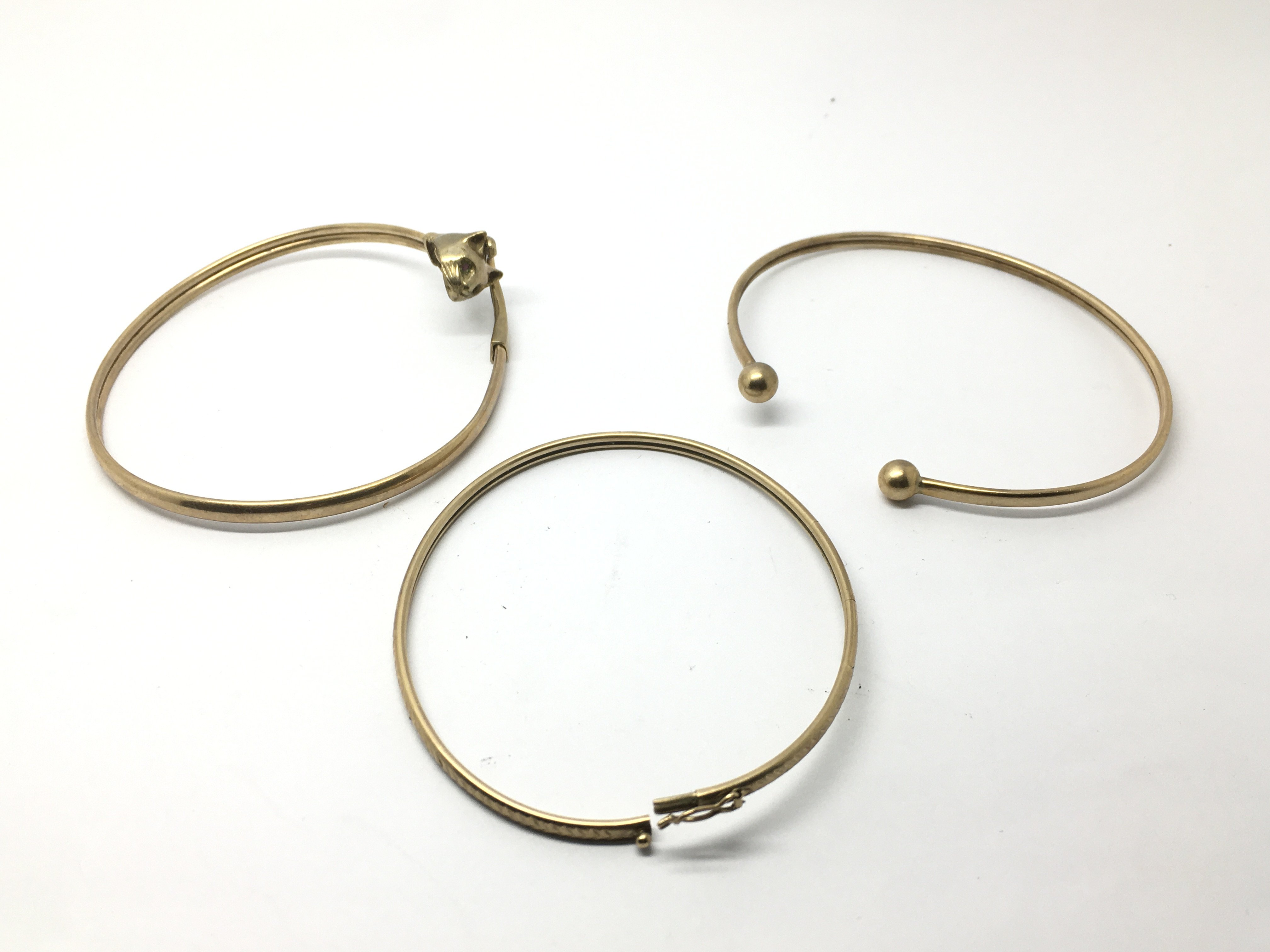 Three 9ct gold bangles, one in the form of a cat's