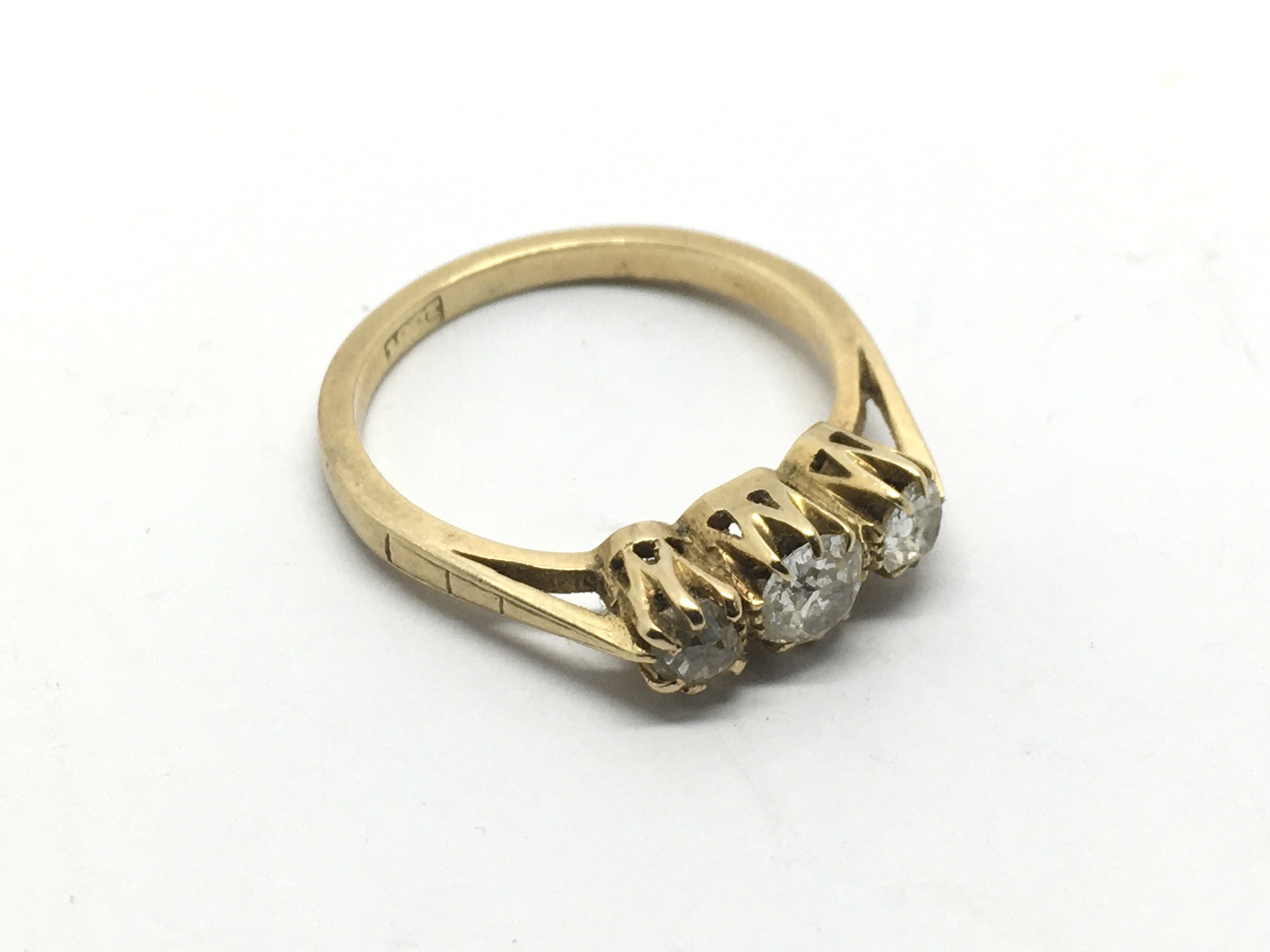 An 18ct gold ring set with three old cut diamonds,