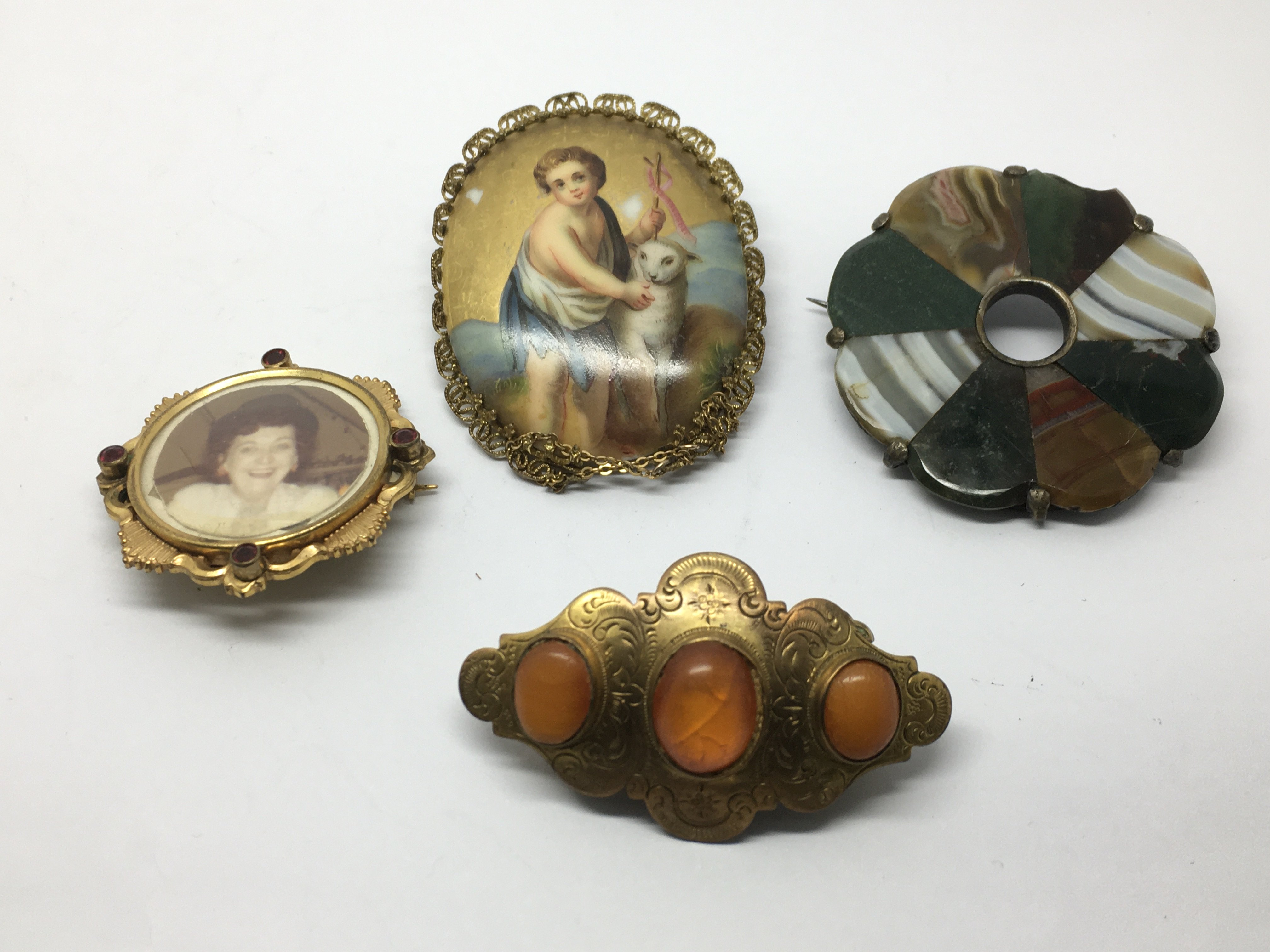 Four brooches, one set with a hand painted porcela
