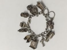 A silver charm bracelet with 12 charms attached. The charms are: a cable car, a fire engine (with