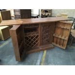 A modern carved Mahogany bar cabinet with a hinged top above cupboards