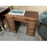 A dark oak pedestal desk with leather inset top.