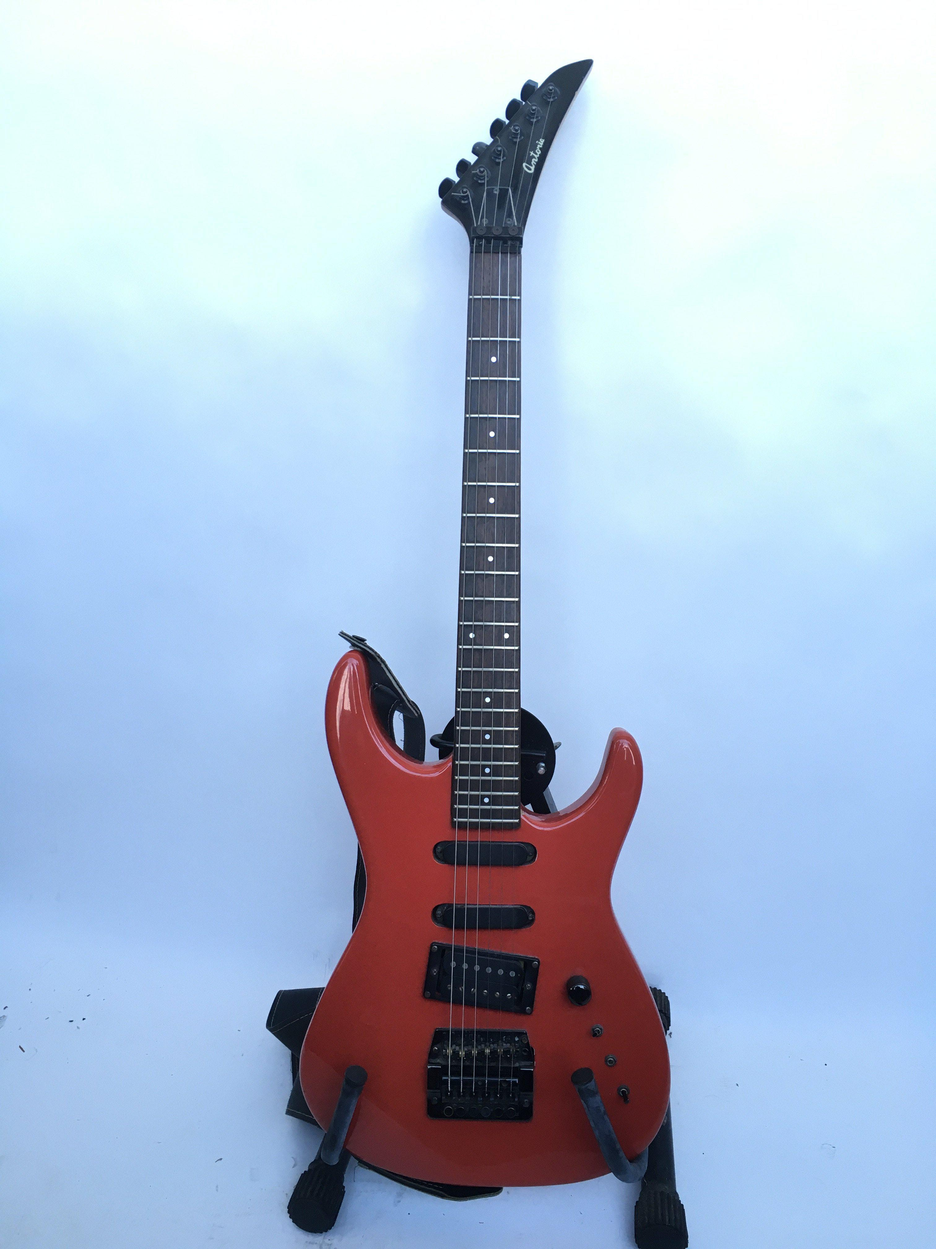 An Antoria electric guitar in red and fitted with